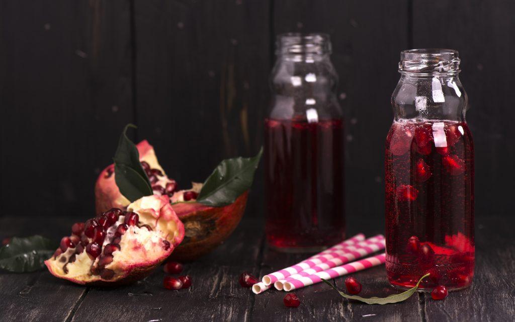 Homemade red pomegranate lemonade in small glass bottles