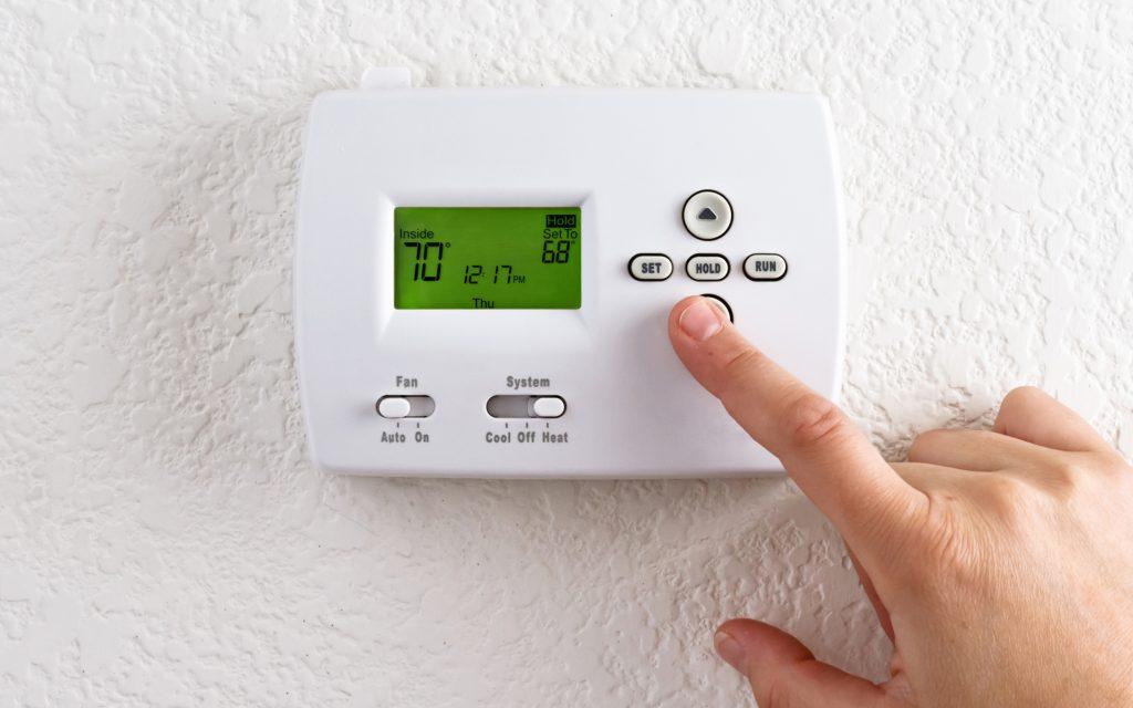 A finger pressing a digital thermostat