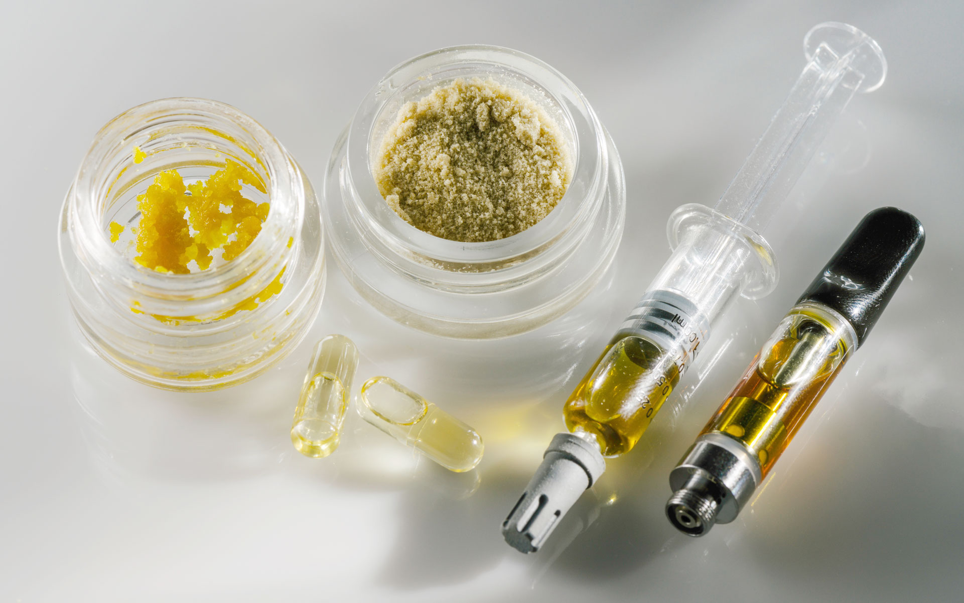 A variety of different cannabis concentrate types on a white background.