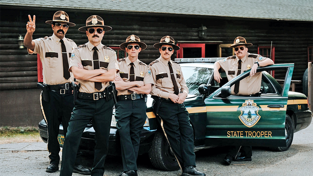 Super Troopers in front of cop car