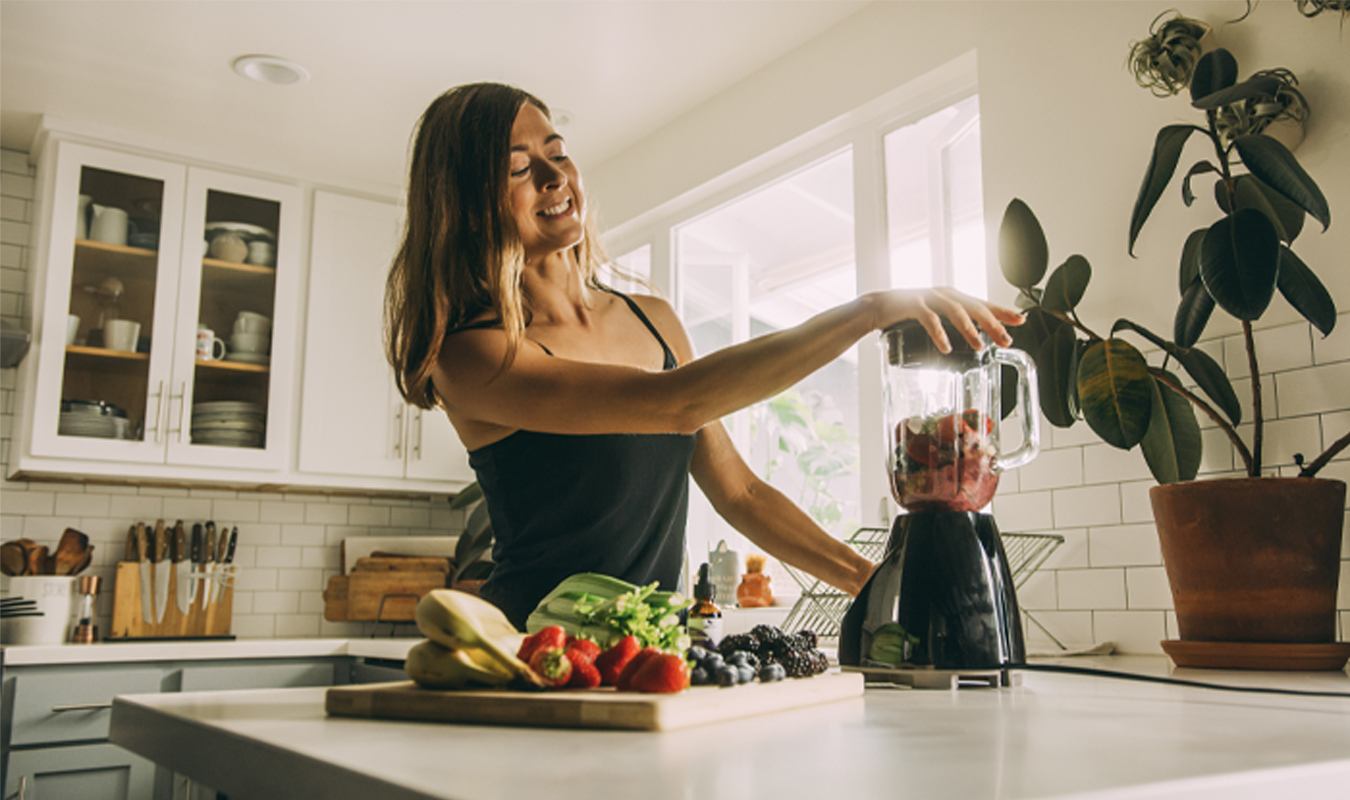 Woman making smoothie in her kitchen with fresh fruits and vegetables