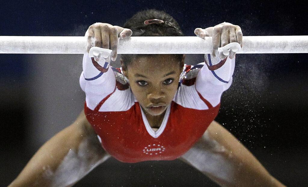Gabby Douglas balanceándose desde la barra de gimnasia.